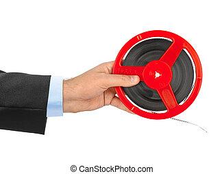 Cinema film reel in hand