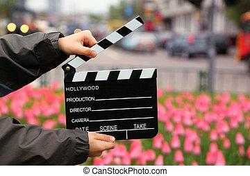 cinema, tábua clapper, em, a, mãos, de, menino, ligado, campo, com, tulips, ligado, urbano, ruas
