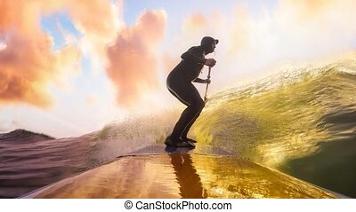 Cinemagraph Continuous Loop Animation. Adventurous Man Surfing the waves at the Pacific Ocean in Tofino, Vancouver Island, British Columbia, Canada. Dramatic Colorful Sunset Sky. Extreme sport