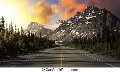 Cinemagraph Continuous Loop Animation. Scenic road in the Canadian Rockies during a vibrant sunny summer sunrise. Sky Composite. Taken in Icefields Parkway, Banff National Park, Alberta, Canada.