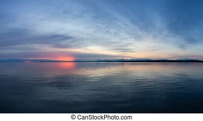 Cinemagraph Continuous Loop Animation. View of the Calm Water on the Pacific Ocean Coast during a colorful cloudy sunset. Taken in White Rock, Vancouver, British Columbia, Canada.
