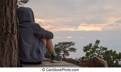 Cinemagraph - girl in a hoodie sits, and contemplates the sky. 4k, time lapse