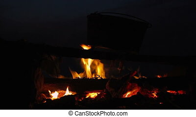Cinemagraph of cooking meal in cauldron on burning campfire...