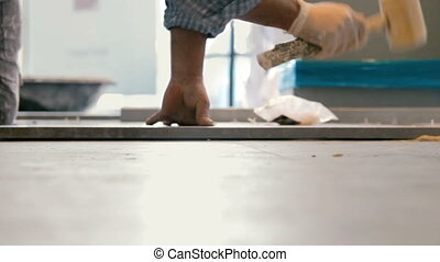 Cinemagraph of worker putting ceramist tile on the floor. He...