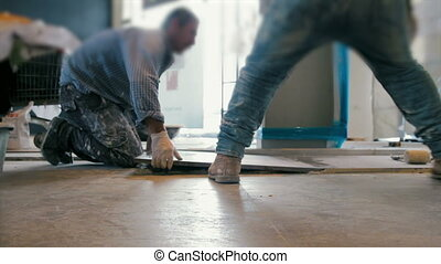 Cinemagraph of workers putting ceramist tile on the floor.
