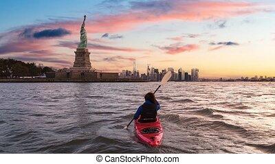 Adventurous Woman Sea Kayaking near the Statue of Liberty