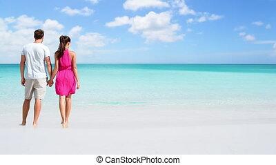 CINEMAGRAPH - seamless loop: Beach couple looking at ocean view from behind