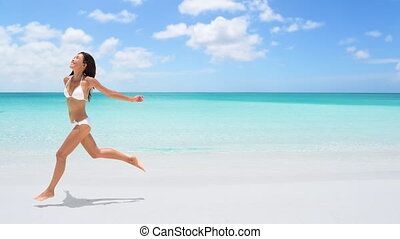 CINEMAGRAPH - seamless loop: Happy woman running on the beach on travel vacation holidays. Image full of aspiration and joy with Caucasian / Asian Chinese bikini model having fun. Looping Motion photo