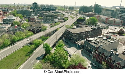 Cinematic aerial tracking shot of vehicles entering the city...