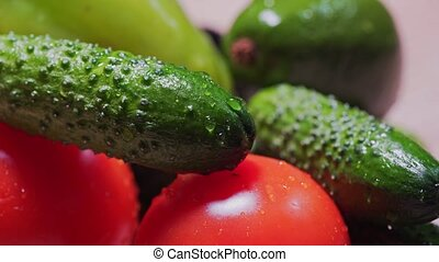 Cinematic drops fall and flow down on cucumbers and tomatoes, MACRO. Organically pure, farm vegetables close-up 4k