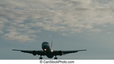 Cinematic shot of a passenger jet airplane about to land. 4K...