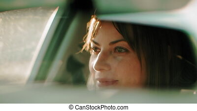 Cinematic shot of a pretty woman driving during the day. 4K...