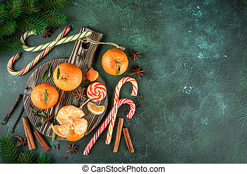 Cinnamon and tangerines with leaves on wooden table