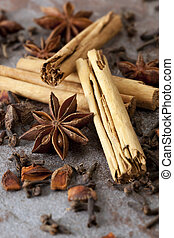 Cinnamon sticks, star anise, and cloves, over stone background. Shallow depth of field.