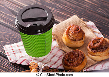 Cinnamon bun and coffee cup on wood background