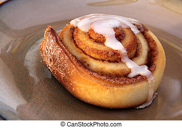 Cinnamon Bun on a Plate - A cinnamon bun sitting on a plate.