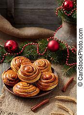 Cinnamon bun rolls christmas sweet dessert on vintage cloth with new year decorations. Traditional swedish kanelbullar baked pastry.