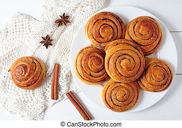 Cinnamon bun rolls christmas sweet dessert on white vintage table. Traditional swedish kanelbullar baked pastry.