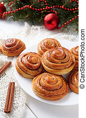 Cinnamon bun rolls christmas sweet dessert on white vintage table with new year decorations. Traditional swedish kanelbullar baked pastry.