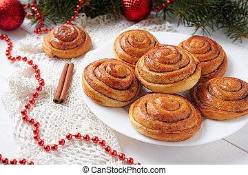 Cinnamon bun rolls homemade christmas sweet dessert on white vintage table with new year decorations. Traditional swedish kanelbullar baked pastry.