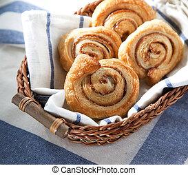 Cinnamon danish bun in the basket on textile background