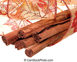 Stack of cinnamon stick wrapped in translucent fall colored ribbon. Shot on white.
