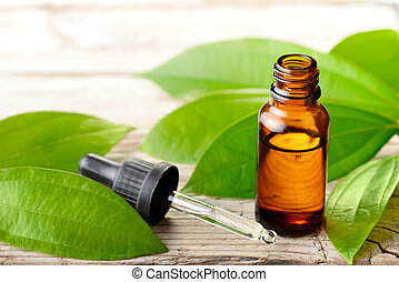 cinnamon leaf essential oil and fresh cinnamon leaves on the wooden board