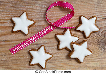 Cinnamon star on wood with Weihnachts - Rezepte (in german Christmas Recipes) gift ribbon