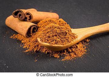 Cinnamon stick and powder on dark background