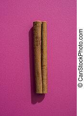 Cinnamon stick - Single cinnamon stick against a pink...