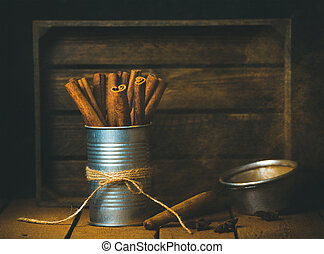 Cinnamon sticks in tin can, rustic wooden background, copy...