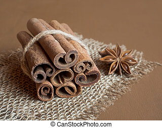Cinnamon sticks linked by a string on burlap Brown wooden background