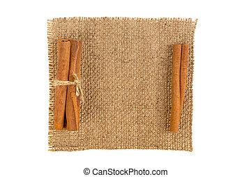 cinnamon sticks on burlap on white background