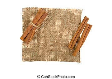 cinnamon sticks on cloth burlap on white background