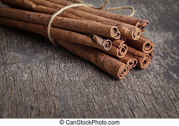 cinnamon sticks on old wooden table, selective focus