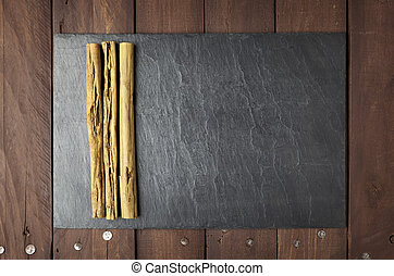 Cinnamon sticks on slate plate with copy space