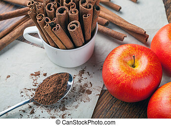 Cinnamon sticks, powder and ripe apples on rustic wooden board top view