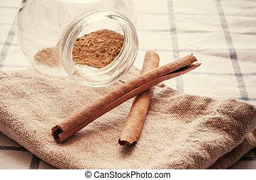 Cinnamon sticks on table cloth. Retro image process.