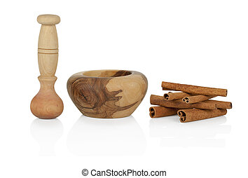 Cinnamon with mortar and pestle on white