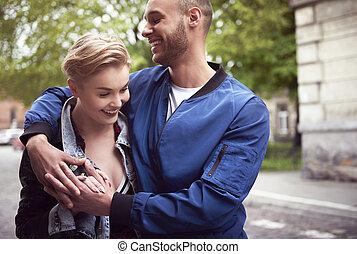 cintura cima, de, par jovem, abraçar, cidade