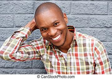 cinzento, parede, jovem, contra, alegre, homem sorridente