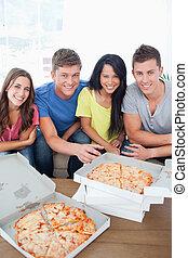 circa, seduta, divano, amici, mangiare, pizza
