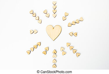 Circle of wooden hearts on white background