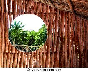 circle window in wooden sticks cabin tropical Jungle -...