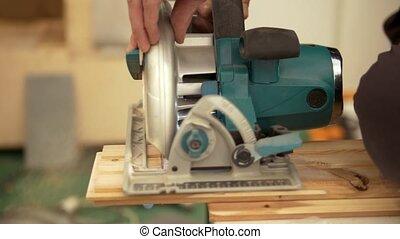Circular blade saw cutting the wooden piece, close up