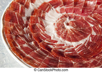 Circular decorative arrangement of iberian cured ham on plate