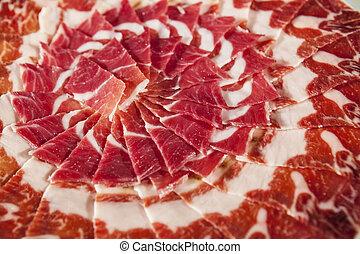 Circular decorative arrangement of iberian cured ham on...