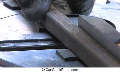 Circular saw blade teeth coming through a steel section,...