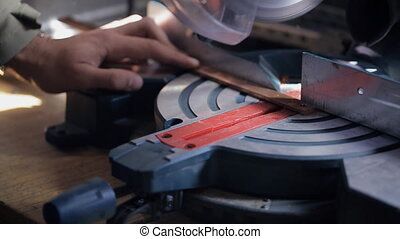 Circular saw cuts the copper bar under the supervision of an employee.