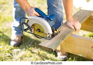 Detail of circular saw cutting piece of wood
